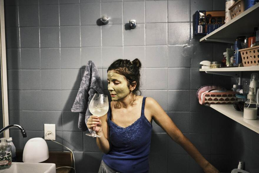 My wife, Priscila, drinks gin and tonic and applies a beauty mask in her bathroom. It's important to still enjoy and take care of ourselves. <em>April 25, 2020. Brasilia, Brazil.</em>