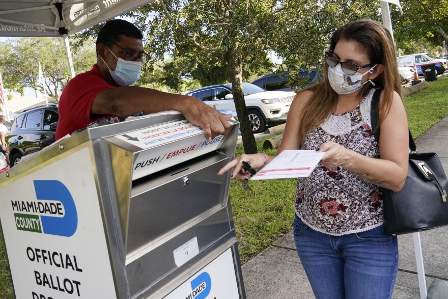 Carlos Amado, left, with the Miami-Dade Supervisor of Elections, guides Isabel Lui to the slot to drop off her ballot, Friday, Oct. 30, 2020 in North Miami, Fla. Early voting in Miami-Dade County ends on Sunday.