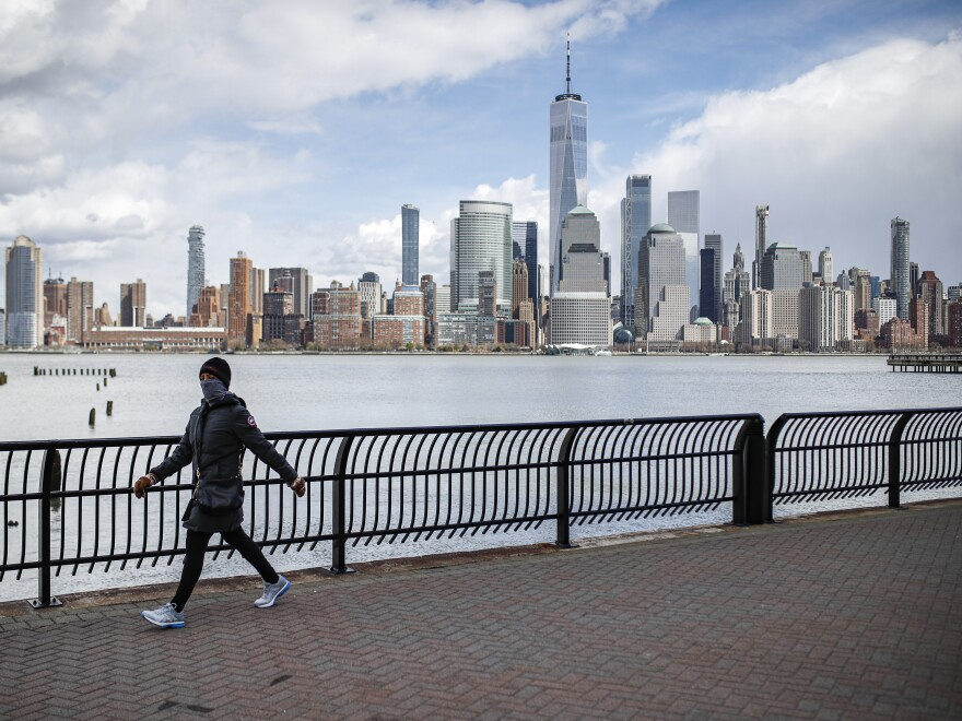 The downtown Manhattan skyline looms over pedestrians wearing masks due to COVID-19 concerns. The New York death toll was 783 over the past 24 hours, Gov. Andrew Cuomo said at a Saturday news conference.