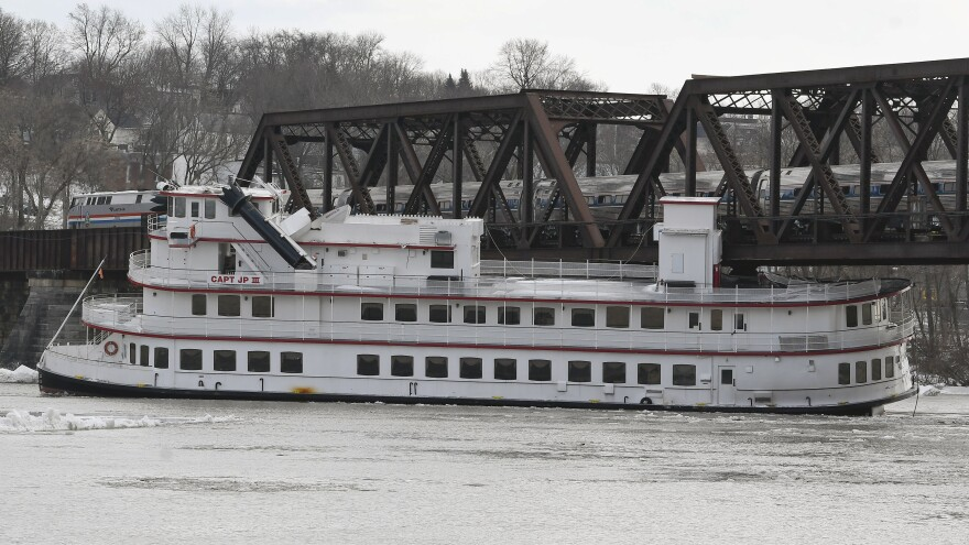A train passes over the Captain JP III cruise ship while it is stuck under a bridge spanning the Hudson River in Albany, N.Y.