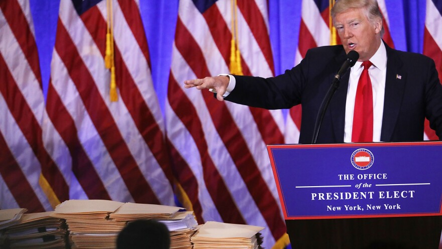 At a Jan. 11 news conference at Trump Tower on in New York City, President-elect Trump gestures at a stack of folders that he said contained documentation separating him from his businesses. That revocable trust was modified about a month later to let Trump withdraw from it at any time, ProPublica reports.