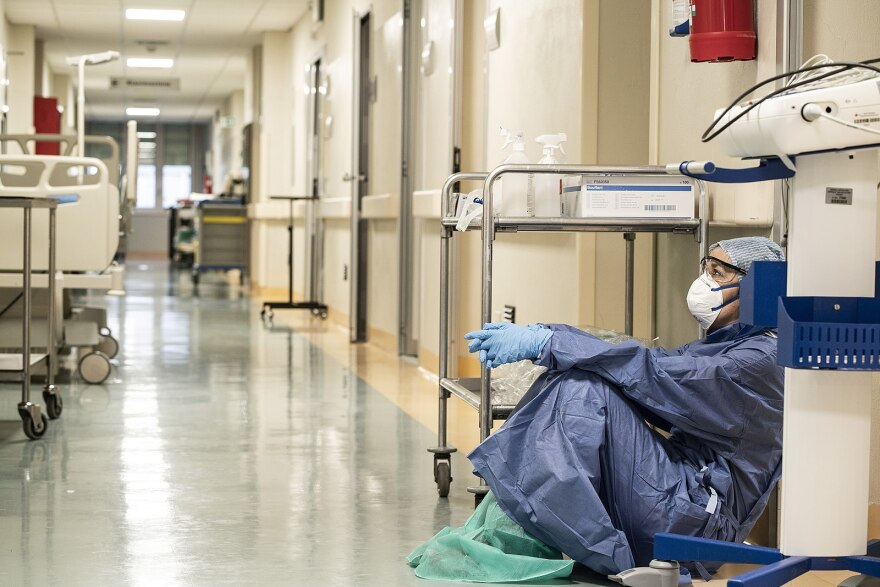 A photo of a doctor in protective COVID gear, sitting in a hospital hallway.