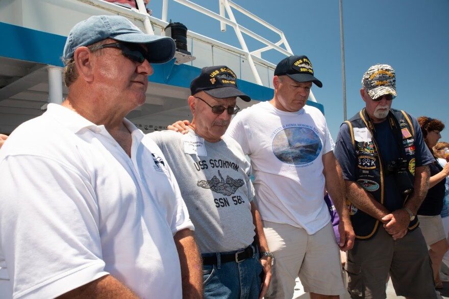 Phil Orapallo (second from left) stands beside fellow submarine veterans at the reef dedication ceremony in May. They bow their heads to remember each ship that was lost.