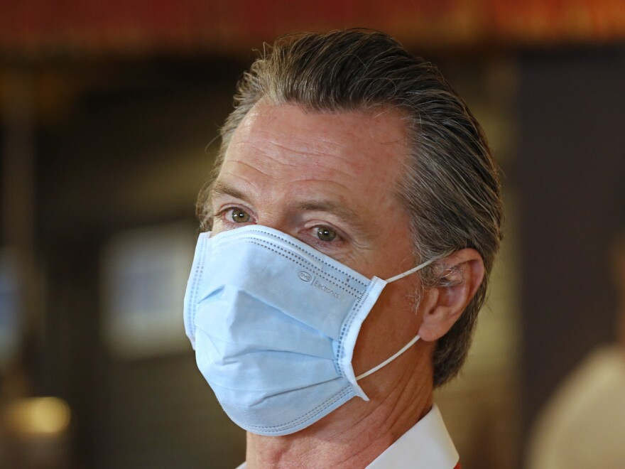 California Gov. Gavin Newsom, here in Sacramento on Friday, has ordered face coverings be required in public spaces statewide.