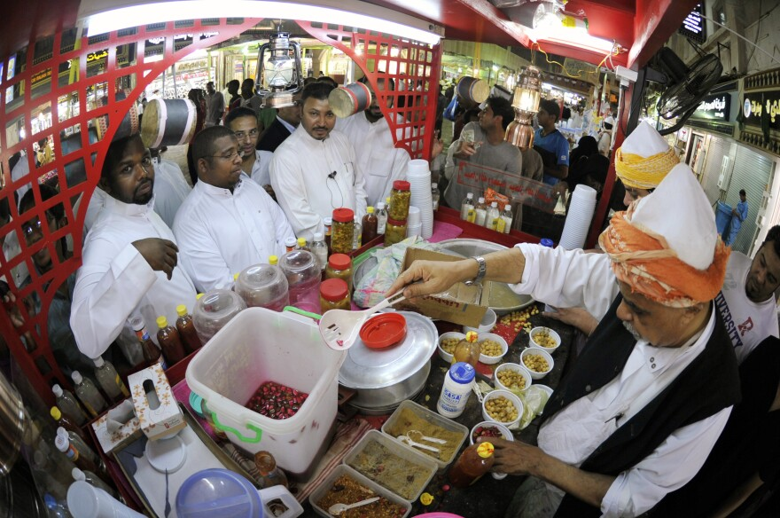 Men line up at a takeaway food stand in the Saudi port of Jeddah in the early hours of August 26, 2011. Practicing Muslims eat their<em> suhoor </em>meal before dawn during the holy fasting month of Ramadan.