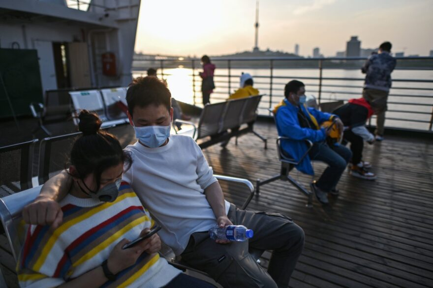 People wearing face masks ride a ferry to cross the Yangtze River in Wuhan in China's central Hubei province after restrictions to halt the COVID-19 coronavirus were lifted.
