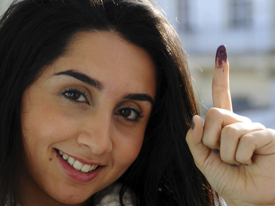 Tunisian voter Dina Ghlisse, 19, displays her finger with the indelible ink mark after voting in La Marsa, on the outskirts of Tunis, on Sunday. More than three years after Tunisia sparked the Arab Spring, the country is choosing a president.