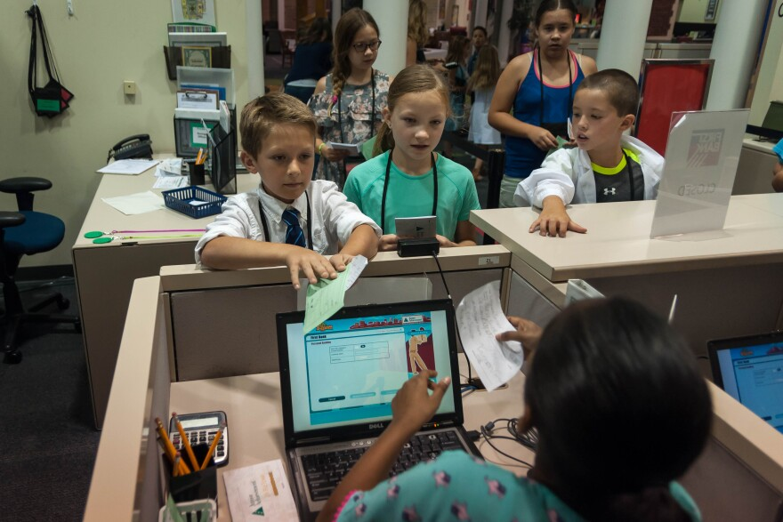 Kids line up to make a deposit at JA BizTown's bank. The residents of BizTown earn a paycheck and must balance the books of the stores they work for the day.