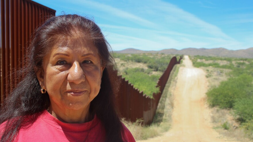 Maria Ochoa poses by the Arizona-Mexico border wall, south of Tucson, Ariz.