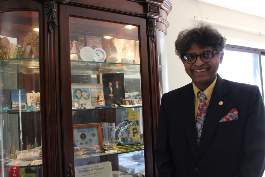 Harold D'Souza stands smiling in front of a display case with pictures of his sons and various awards and medals. He is wearing a black suit with a red tie and glasses.
