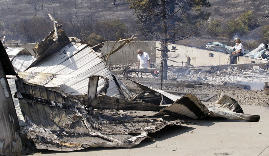 As embers still smolder, family members sift through the remains of their home that was destroyed in a wildfire.