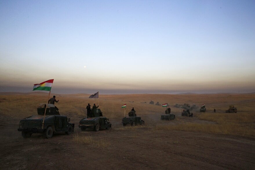 A Peshmerga convoy drives toward a frontline on Monday in Khazer, about 19 miles east of Mosul, Iraq.
