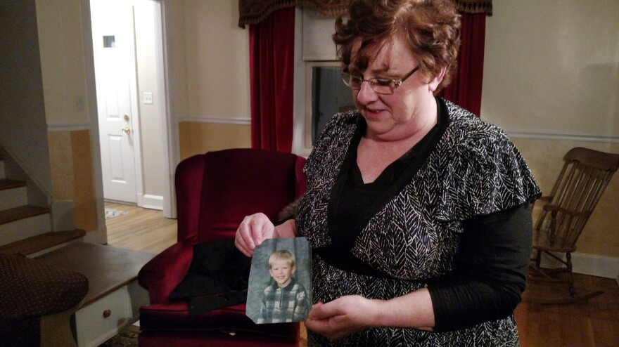 "Toni Hoy, at her home in Rantoul, Ill., holds a childhood photo of her son, Daniel, who is now 24. In a last-ditch effort to get Daniel treatment for his severe mental illness in 2007, the Hoys surrendered parental custody to the state. ""When I think of him, that's the picture I see in my mind. Just this adorable, blue-eyed, blond little sweetie,"" Hoy says."