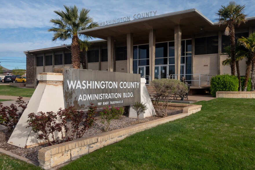 The entrance of the Washington County Administrative Building is framed between two palm trees. A large sign sits out front.