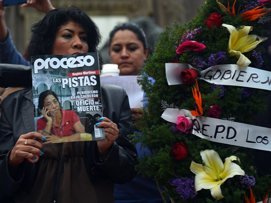 A mourner holds up a copy of <em>Proceso</em> magazine with investigative reporter Regina Martinez on its cover at the vigil in Mexico City last week. At the end of April, Martinez's body was found in her bathroom, beaten and strangled.