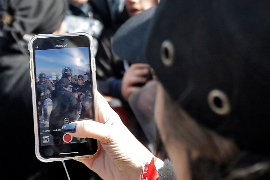 A woman films with her phone as Lebanese security forces detain an anti-government protester during clashes in a demonstration in Beirut in January.