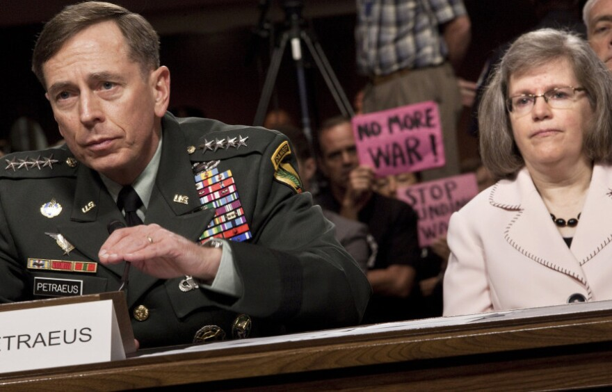Gen. David Petraeus, the top military commander in Afghanistan, speaks during his confirmation hearing before the Senate Armed Services Committee last June as his wife, Holly, listens.