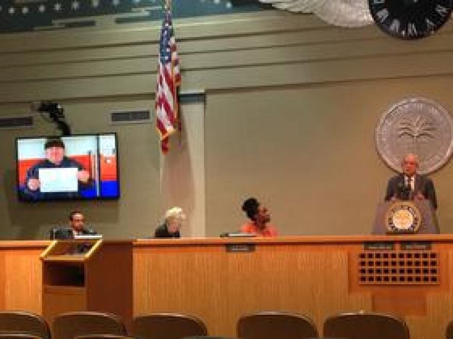 """Miami Mayor Tomás Regalado addressing the issue of Medicaid expansion. On the monitors there's a photo of an uninsured man with a sign that says """"no insurance"""". Harry Melo (also pictured) falls under the coverage gap and is also not insured."""