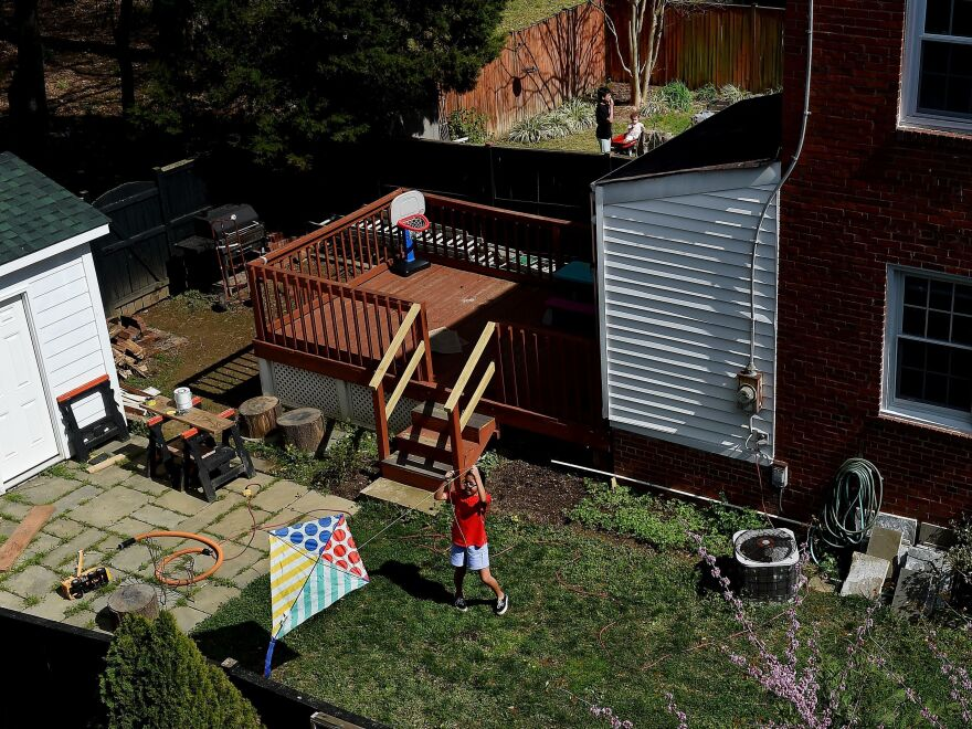 A child attempts to fly a kite in the backyard in Arlington, Va. on April 9, with nearby parks closed due to the coronavirus outbreak and orders to stay at home. As summer begins, many are wondering what they can do if they can't travel because of the pandemic.