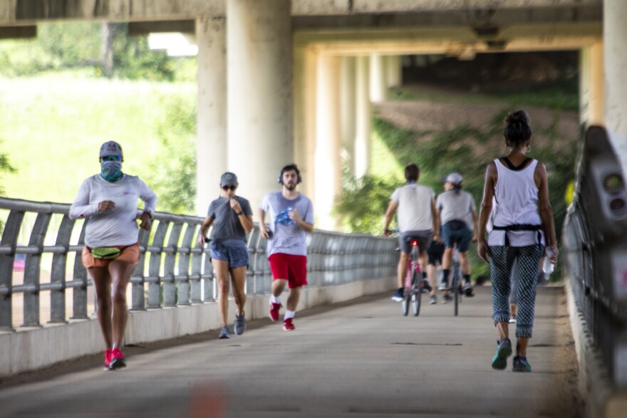 Some people wear face coverings while exercising along the Butler Hike-and-Bike Trail in Austin.