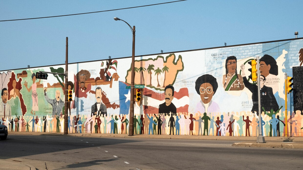 A mural showing Mexican, Puerto Rican, Native American and Black historic icons is displayed near the industrial corridor of Walker Square in Milwaukee