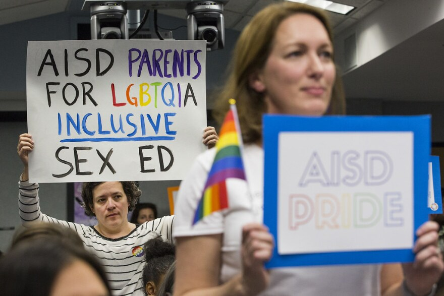 Erika Bodoin (left) holds a sign in support of adopting National Sexual Education Standards at an AISD Board meeting on Feb. 25.