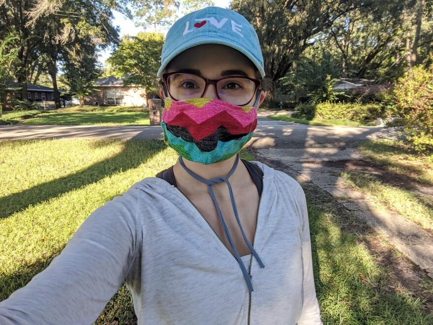 women in glasses taking an outdoor selfie, wearing colorful mask