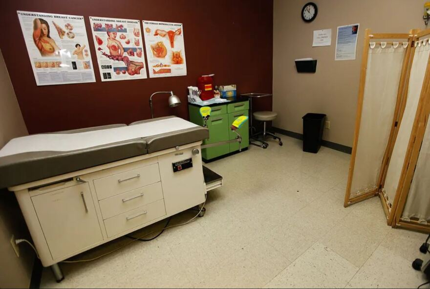 A room inside a doctor's office. Posters with diagrams about women's health on the walls.