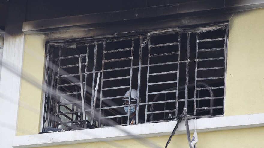 A forensic police officer investigates a dormitory window at a religious school in Malaysia after a fire that killed about two dozen people Thursday.