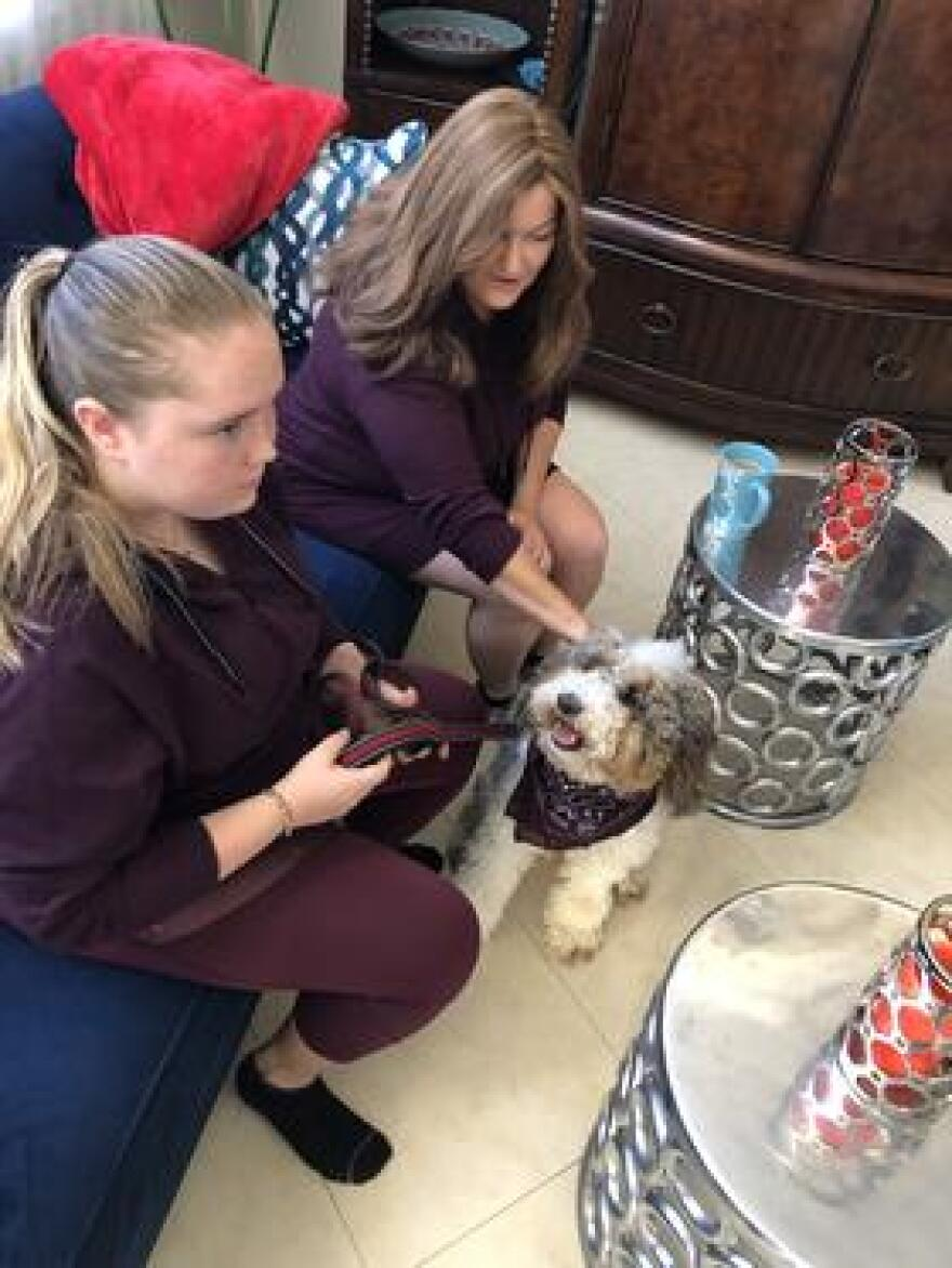 Annabel Claprood, 17, and her mom, Elyse, are next to each other on the couch in their living room in Coral Springs. River, the therapy dog who works in the library at Marjory Stoneman Douglas High School, sits at their feet.