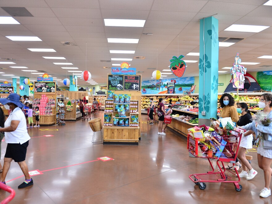 Trader Joe's says it is in the process of discontinuing some of its product branding. Here, shoppers buy groceries at a store last week in Pembroke Pines, Fla.