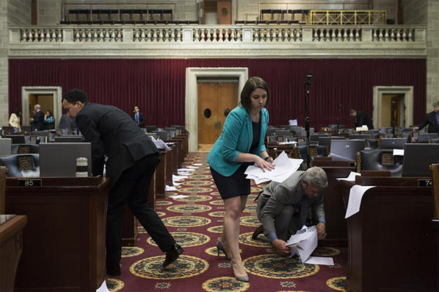 Rep. Crystal Quade picks up papers left on the floor after legislators threw them in the air to mark the end of the legislative session.
