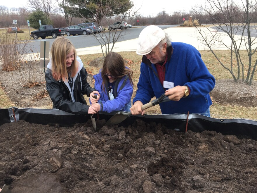 Kiwanis Club of Blue Ridge West Virginia member Roger Ethier helps two students dig in the dirt.