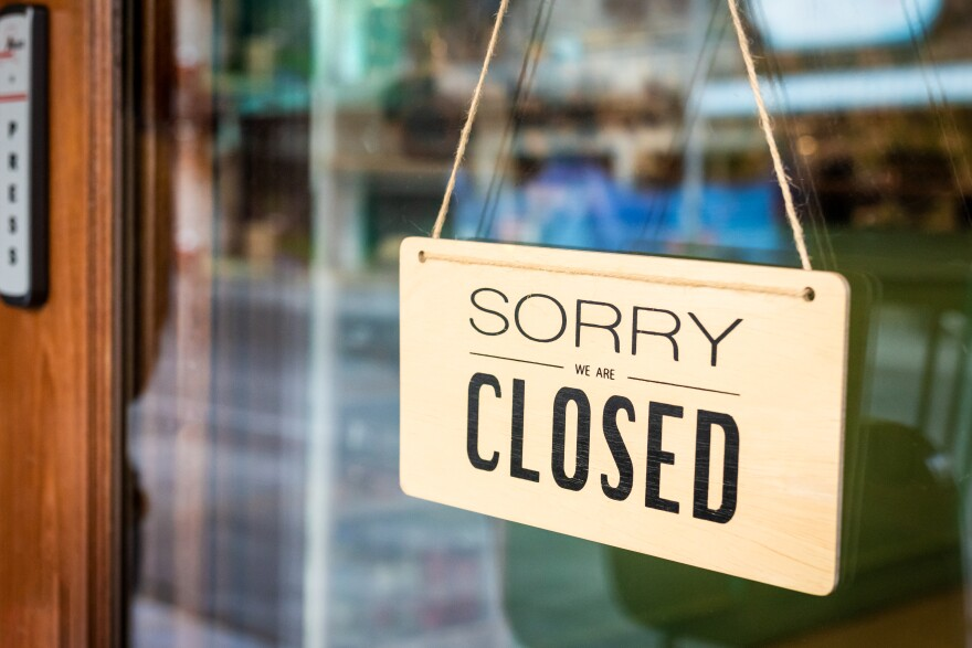 sign on a restaurant door says sorry we're closed.