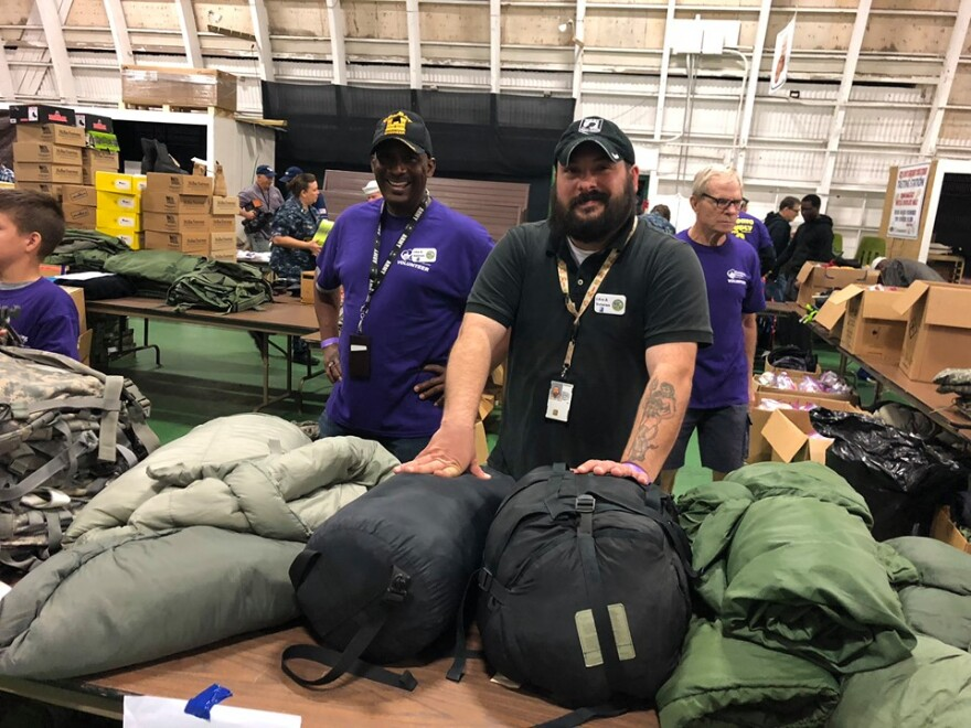 Men standing at table with sleeping bags for distribution.