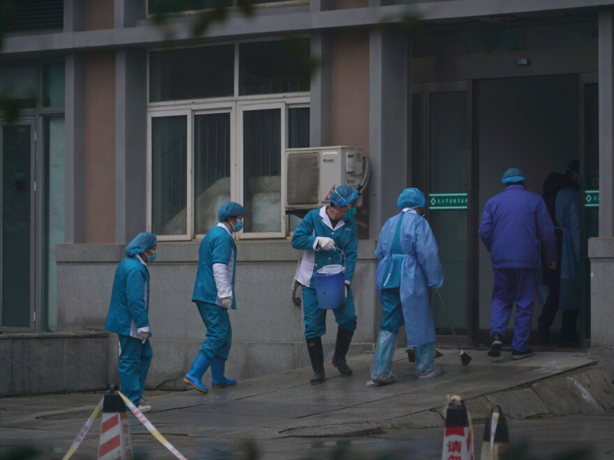 Hospital staff wash the emergency entrance of Wuhan Medical Treatment Center, where patients infected with a new virus are being treated, in Wuhan, China, on Wednesday.