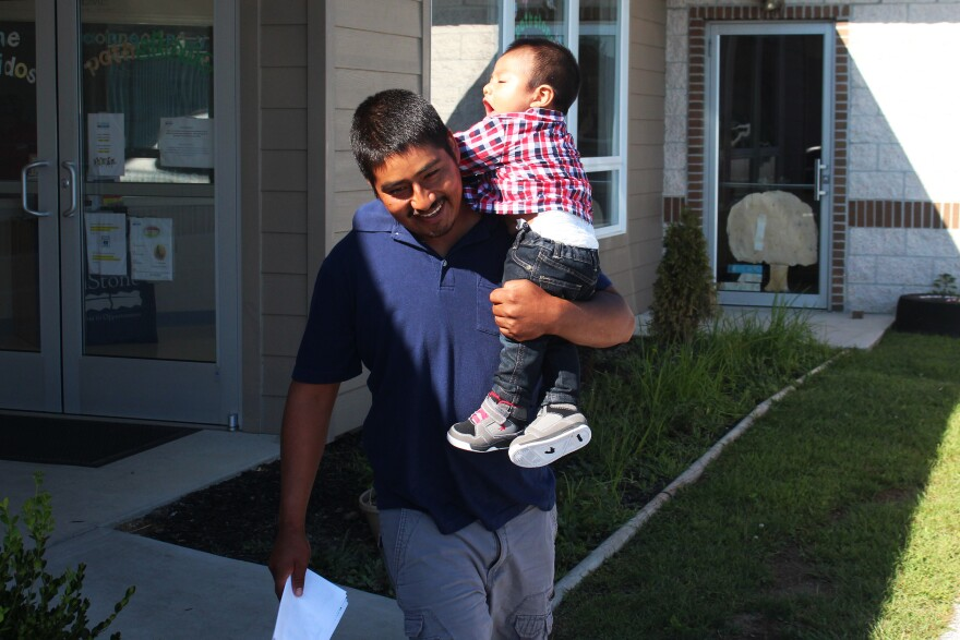 """Martinez carries his toddler son, Richard, from the Head Start school building. The family spends about half the year in Florida, where there's work through the winter. That's the closest approximation of """"home."""" The rest of the year, the children move from one school or preschool to another."""