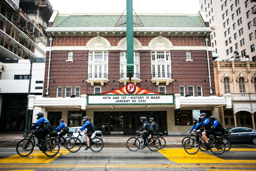 """A group of Austin police officers on bicycles rides past the Paramount Theatre, where the marque reads: """"46th and 1st – History is made. January 20, 2021."""