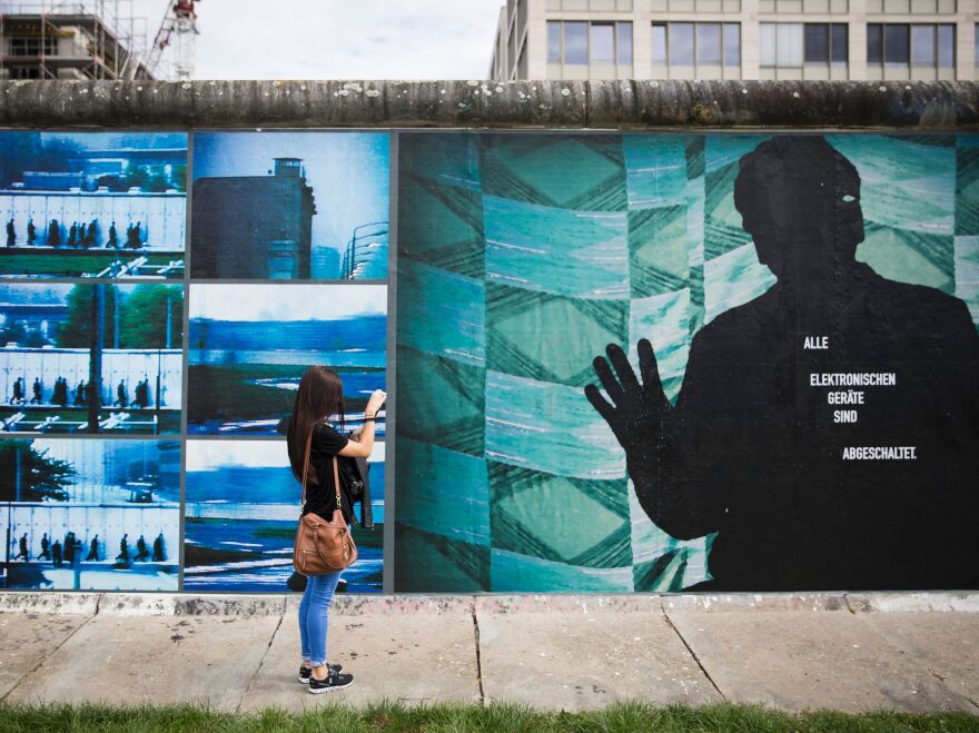 """A woman takes pictures of the installation """"Beyond The Wall"""" by German artist Stefan Roloff mounted on remnants of the former Berlin Wall earlier this month."""