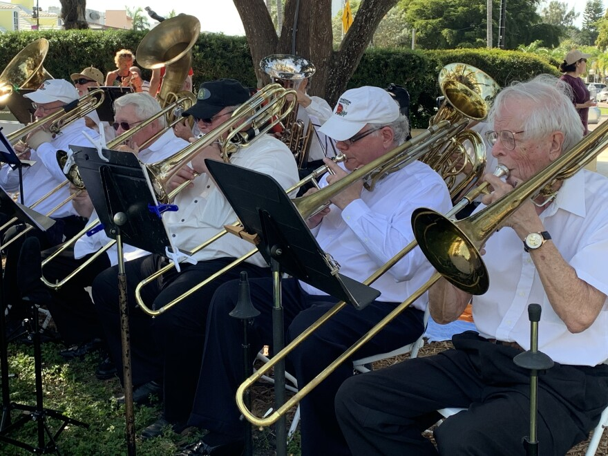 Men play trombones at outdoor concert