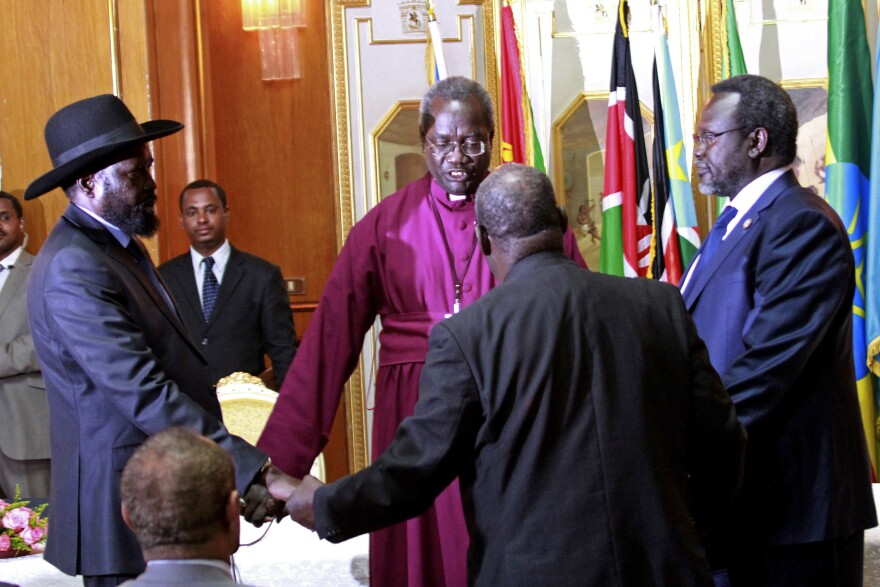 South Sudan's President Salva Kiir (left) and rebel leader Riek Machar (right) shake hands and pray before signing an agreement of the cease-fire of the South Sudan conflict on Friday in Addis Ababa, Ethiopia.