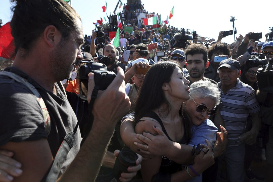 A woman who supports migrants embraces another supporter to help her leave the area so as not to be attacked by demonstrators protesting the presence of thousands of Central American migrants in Tijuana, Mexico, Sunday, Nov. 18, 2018.