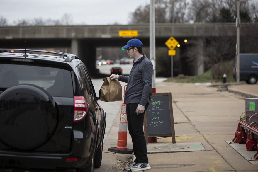An employee brings food to customers outside Indo on Tower Grove Avenue on March 20, 2020.