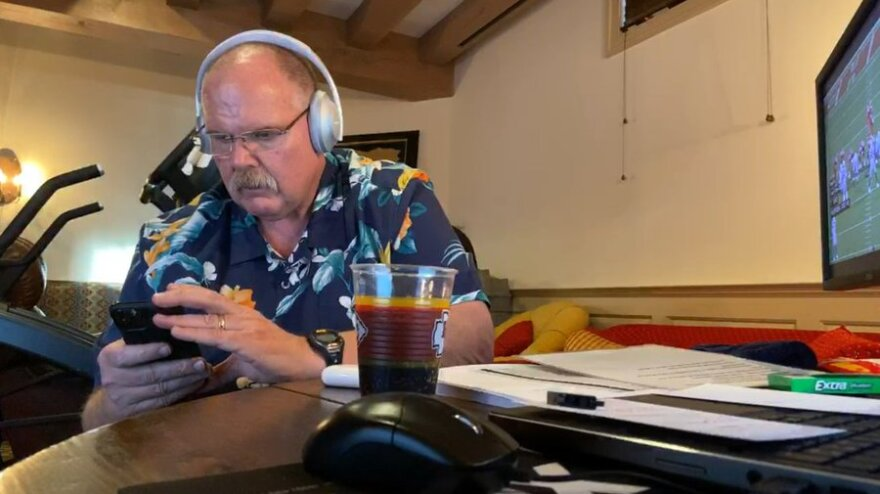Picture of Andy Reid wearing headphones and a Hawaiian shirt as he participates in the NFL draft from home
