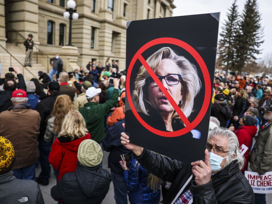 A man holds up a sign against Rep. Liz Cheney, R-Wy., as Rep. Matt Gaetz, R-Fla., speaks to a crowd during a rally against her on Thursday in Cheyenne, Wyoming.