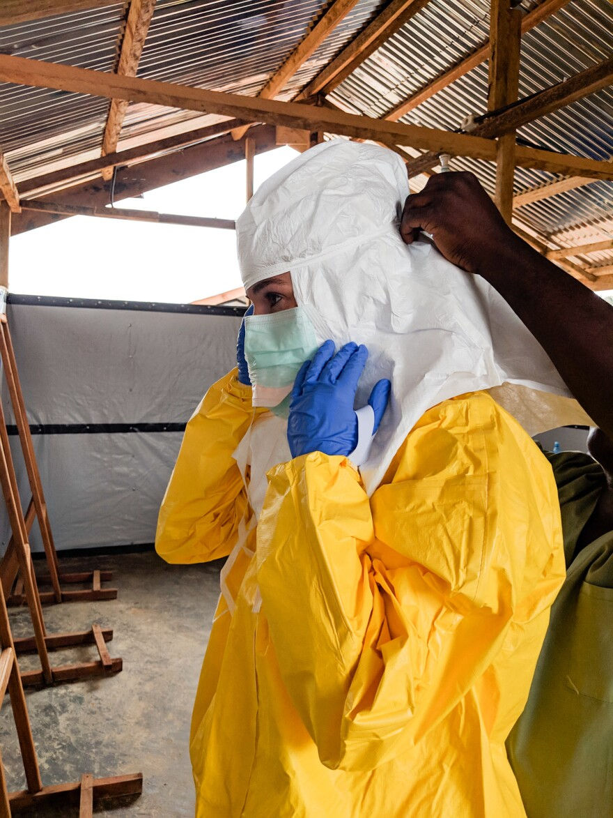 Karin Huster donning her protective gear in an Ebola ward, where medical teams tried to come up with ways to compensate for the lack of human touch.