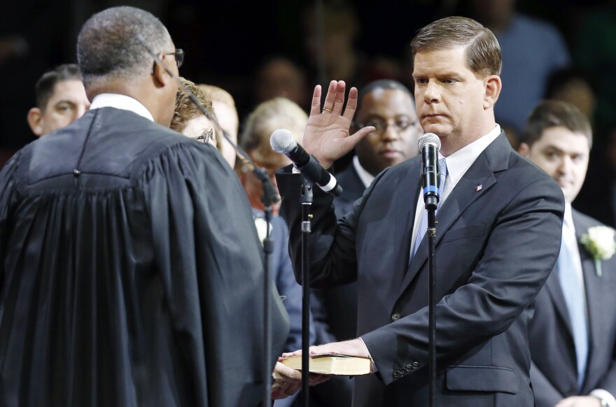Mayor-elect of Boston, Marty Walsh (right), takes the oath of office Monday in Conte Forum at Boston College.