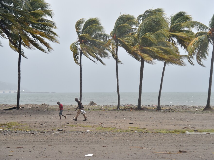 People walk through the wind and rain on a beach in Cap-Haitien on Thursday, as Hurricane Irma approaches.