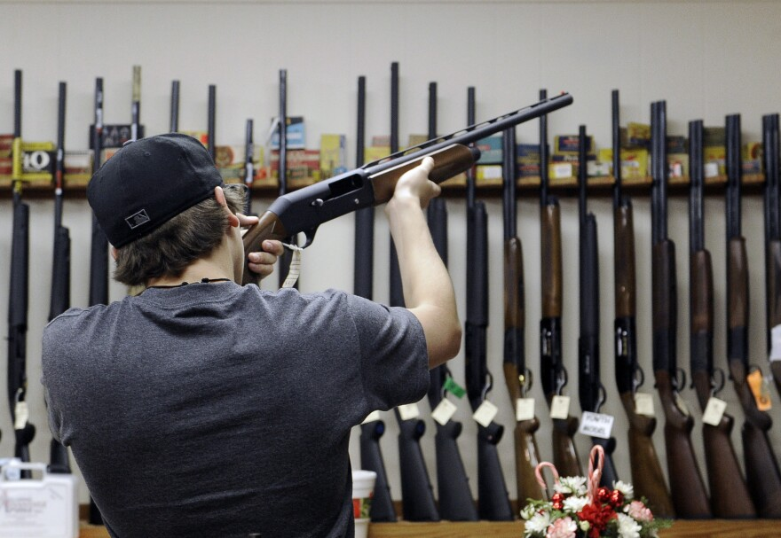 A customer checks out a shotgun at a store in College Station, Texas.