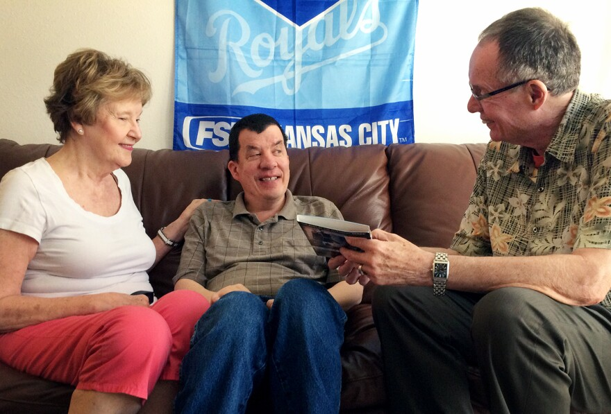 Nick Fugate (center) with his parents, Julie and Ron, has been adjusting to life on Kansas' waiting list to get life-assistance services through Medicaid.